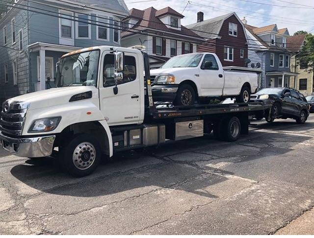 White flatbed tow truck towing pickup truck